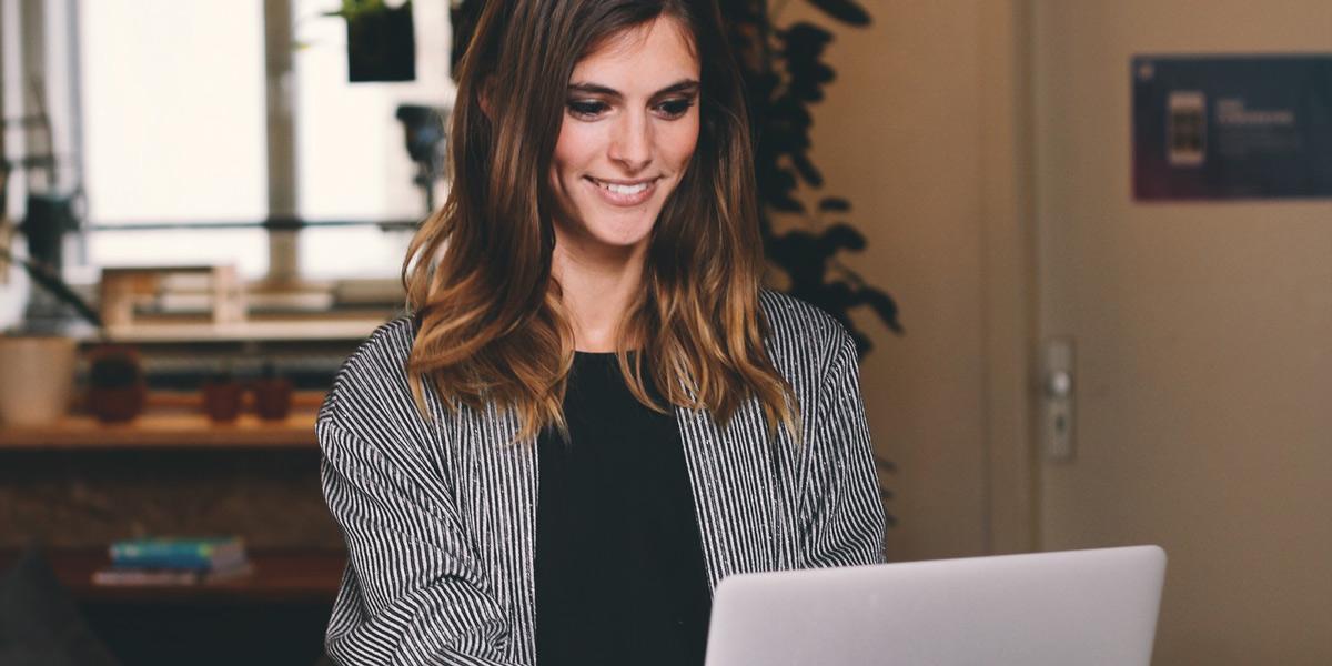 A designer sitting at her desk, smiling at her laptop screen