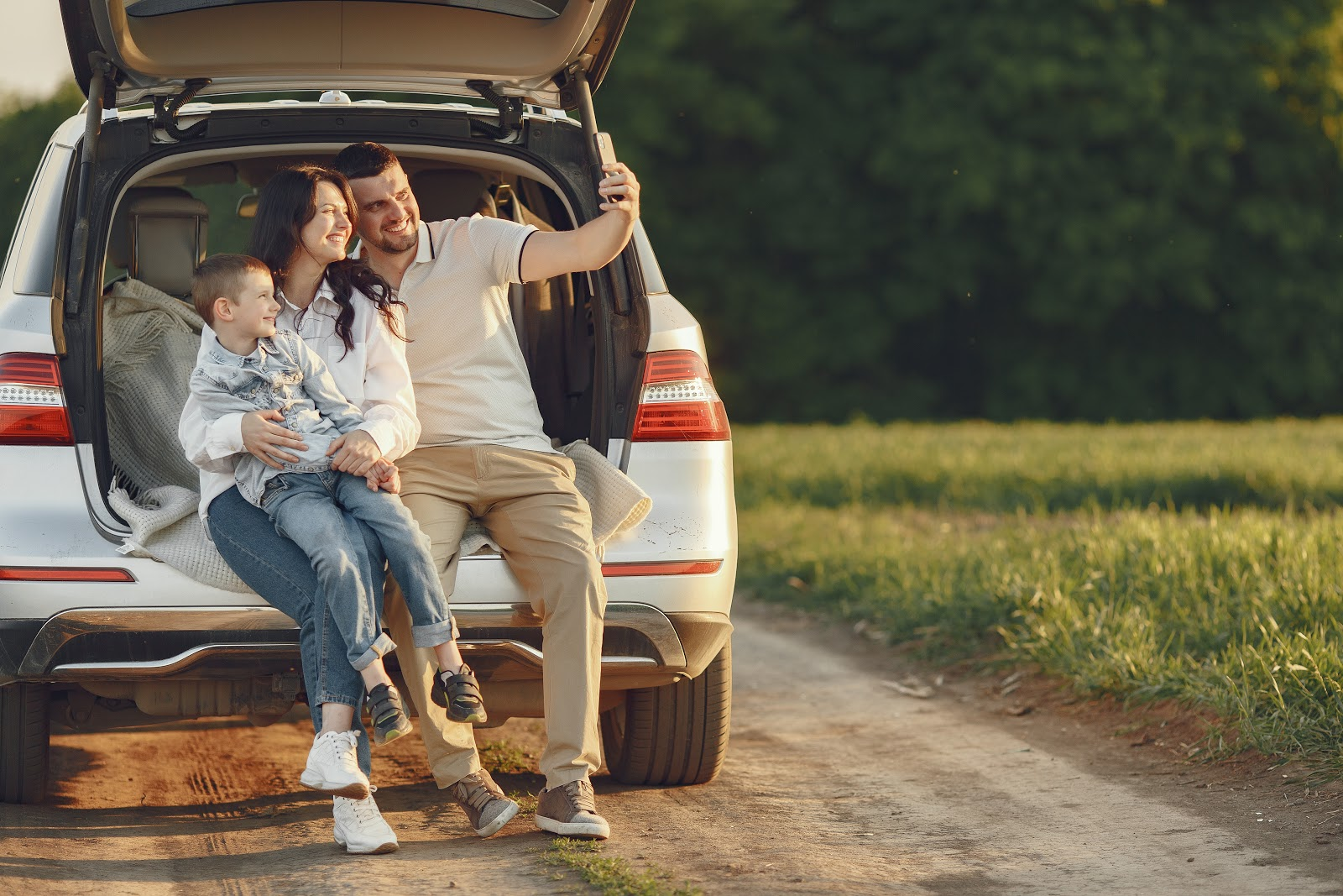 Family taking photo in open trunk of car