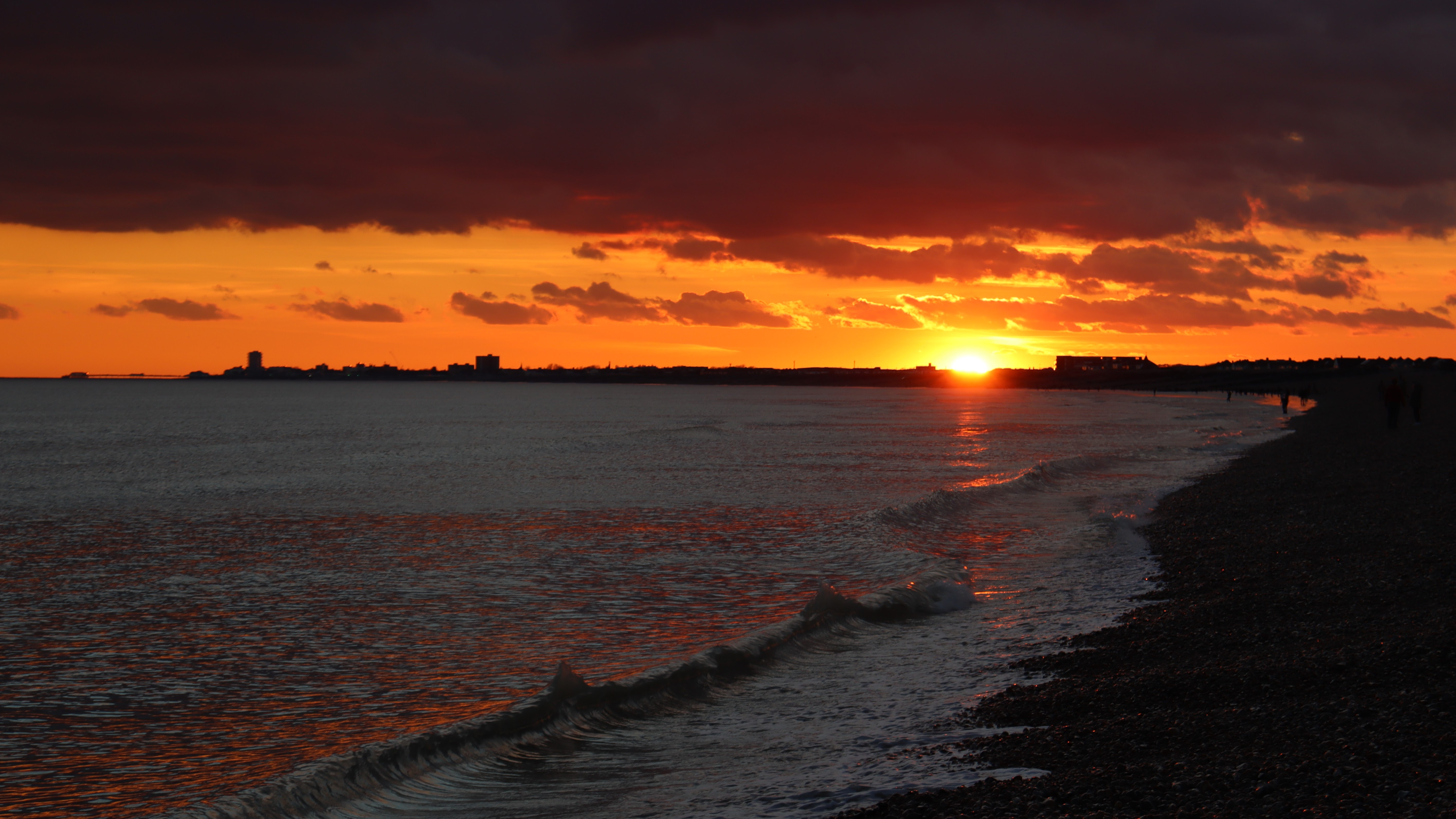 Red sunset beneath a black cloud over the beach.