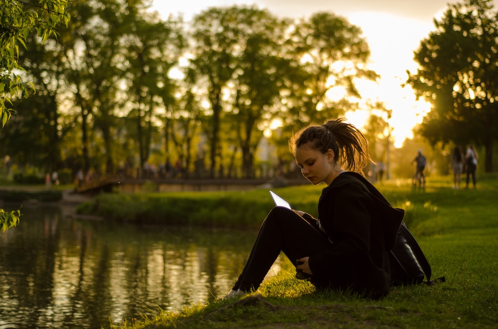 woman sitting on grass field beside body of water during golden hour. Photo by Vadim Fomenok on Unsplash