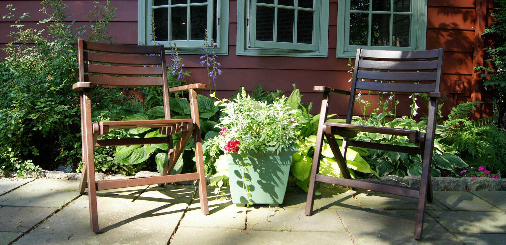 two chairs with flower pot in between them