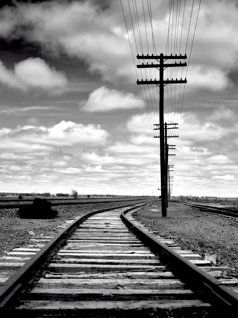 photo of a power line next to a railroad trailing off into the horizon