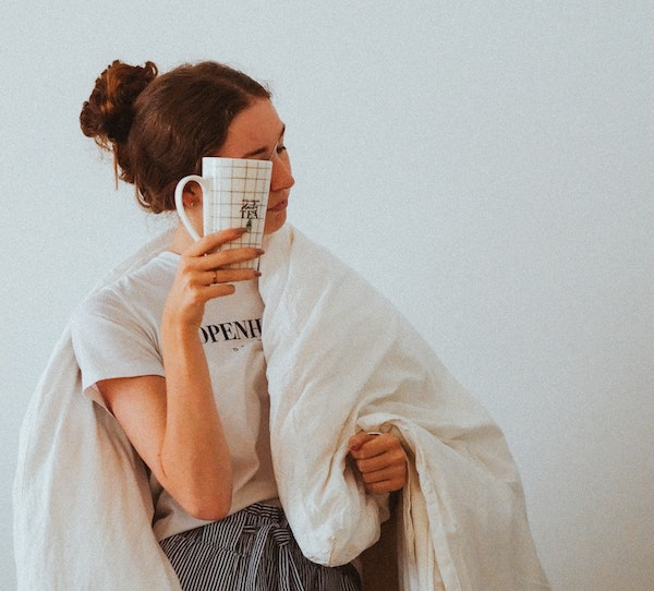 mujer con edredon y cafe
