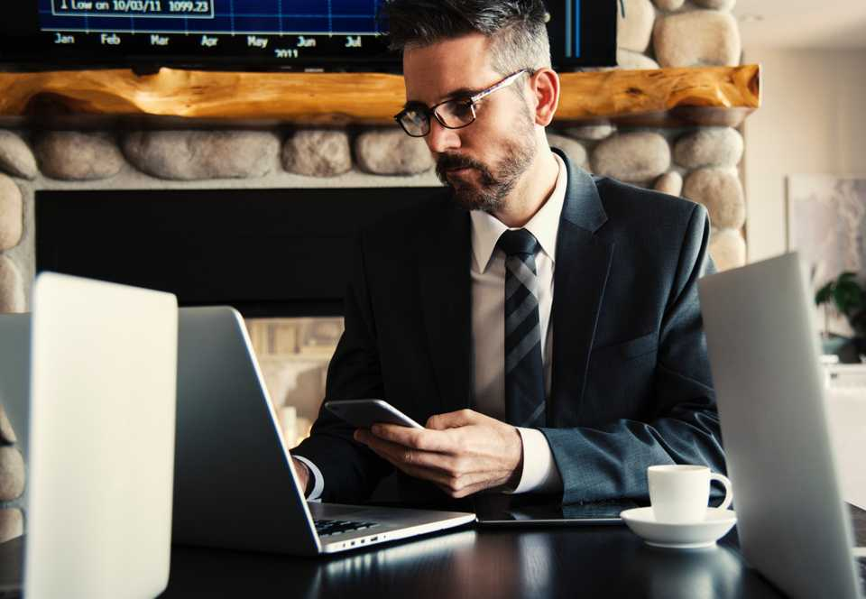 Man works on his phone and laptop doing finance as an accountant in a suit in front of a fireplace