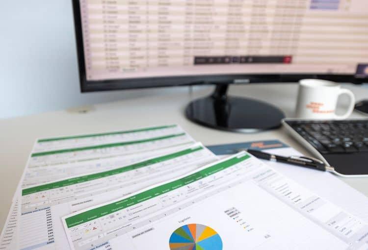 Bildschirm mit Excel-Übung und ausgedruckten Excel-Schulungsunterlagen