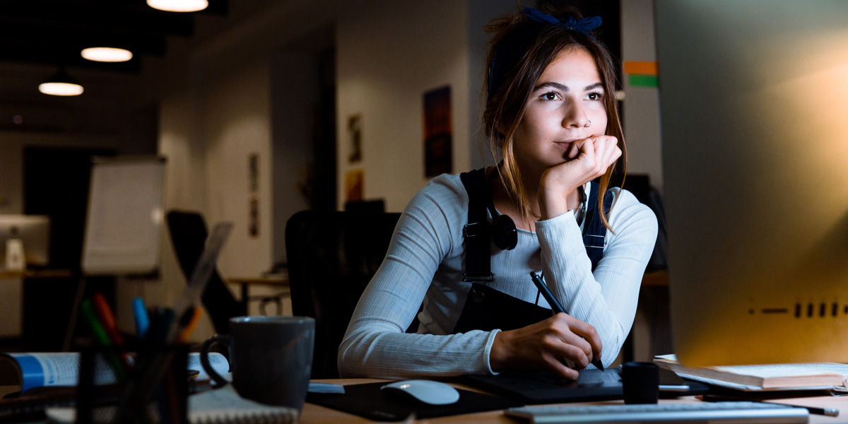 An aspiring UX writer sitting at a desk with a lamp, taking notes in front of a screen.