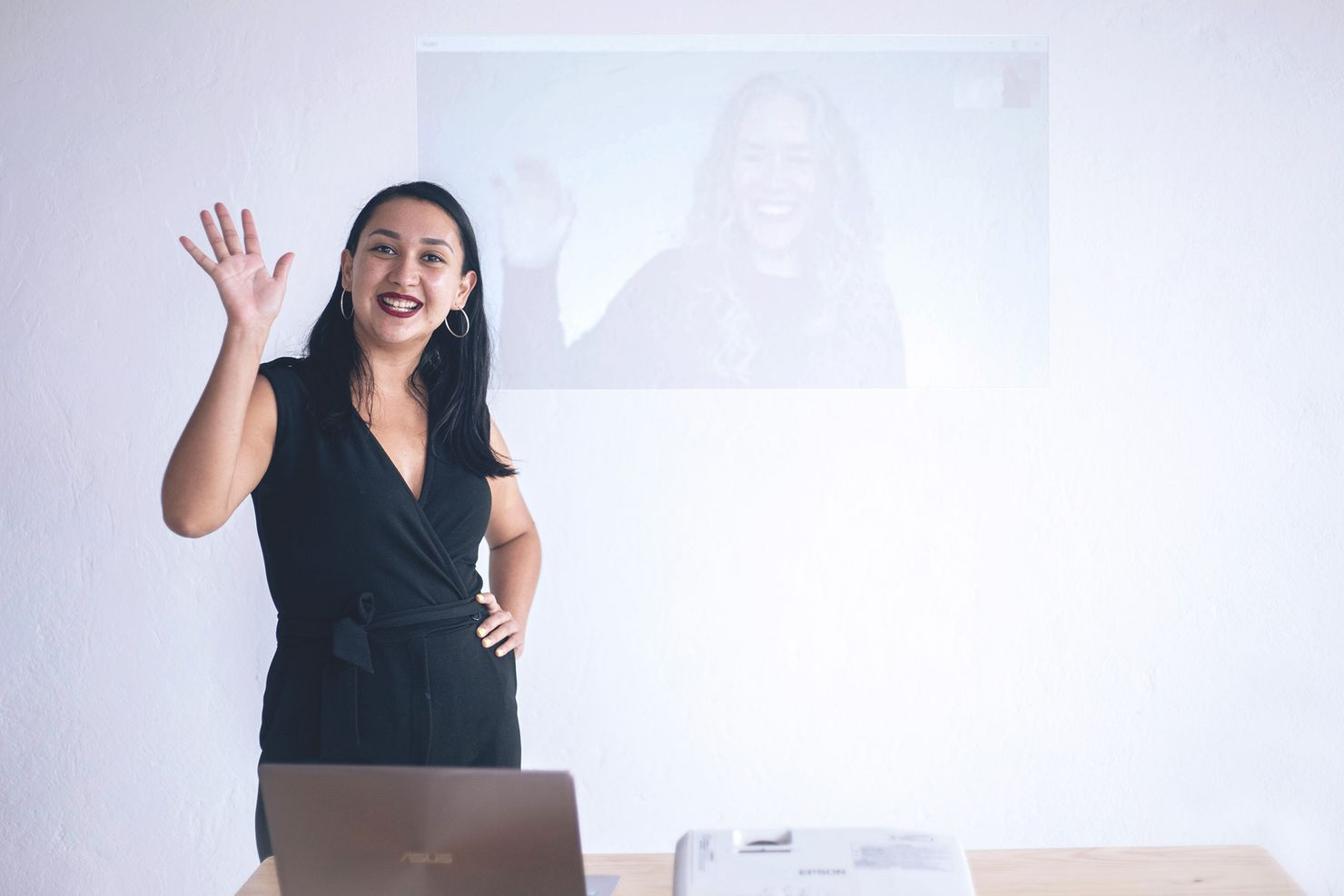ta corrales and liz hunt (whose image is projected on the wall behind ta) wave during one of Smith Assembly's workshops