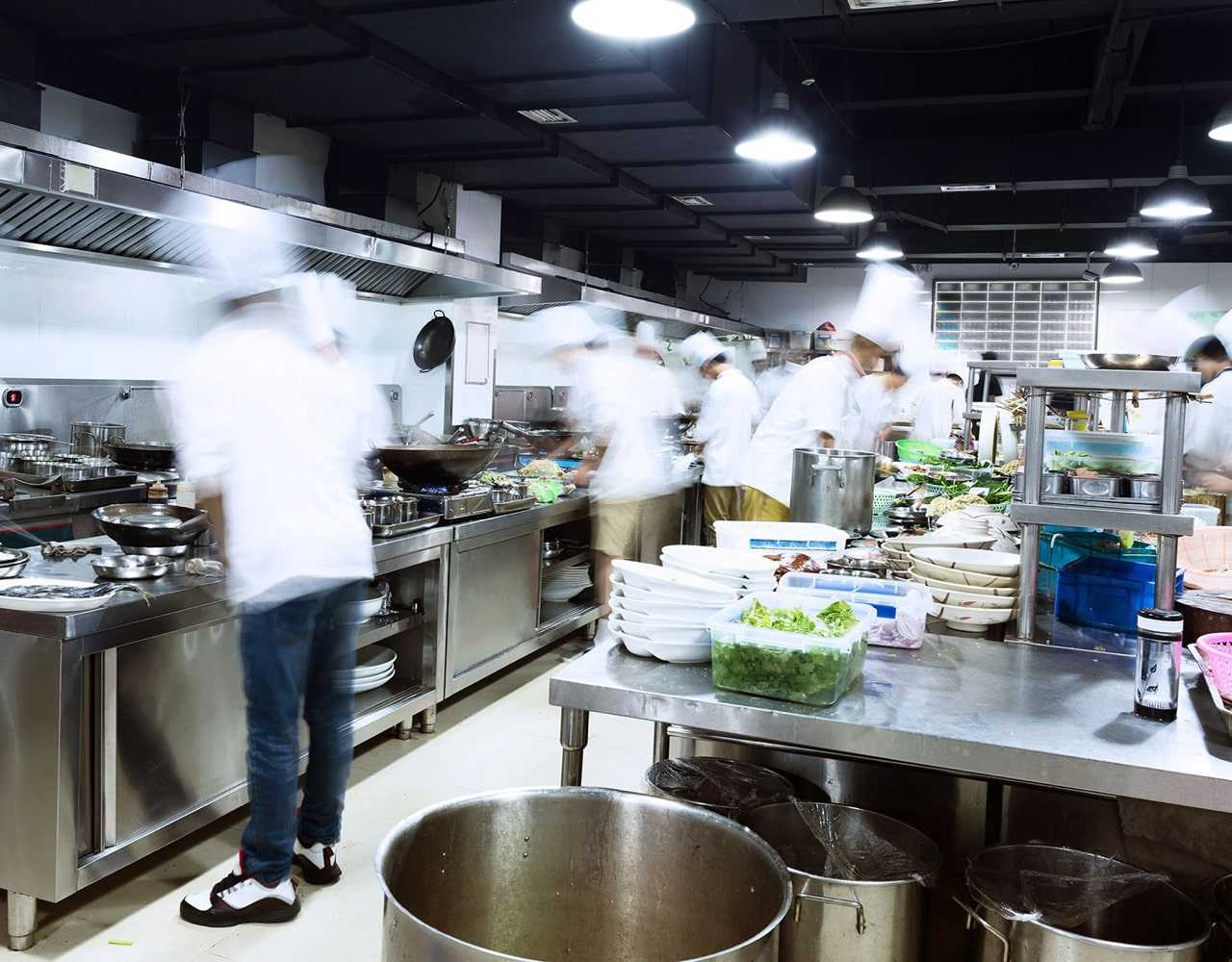Cooks preparing food in a commercial kitchen.