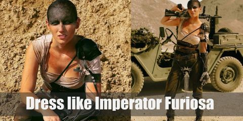 Furiosa wears a tan short-sleeved blouse, a girdle, a leather belt, brown trousers, black motorcycle boots, and an iconic shoulder pad.