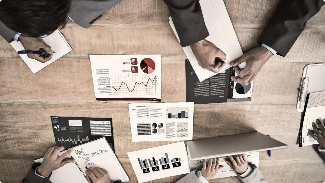 Sécurité au travail - Une table de réunion vue de haut ou l'on voit des documents présentant des graphiques posés sur la table, 3 employés prennent des notes, le quatrième tape sur le clavier d'un ordinateur portable