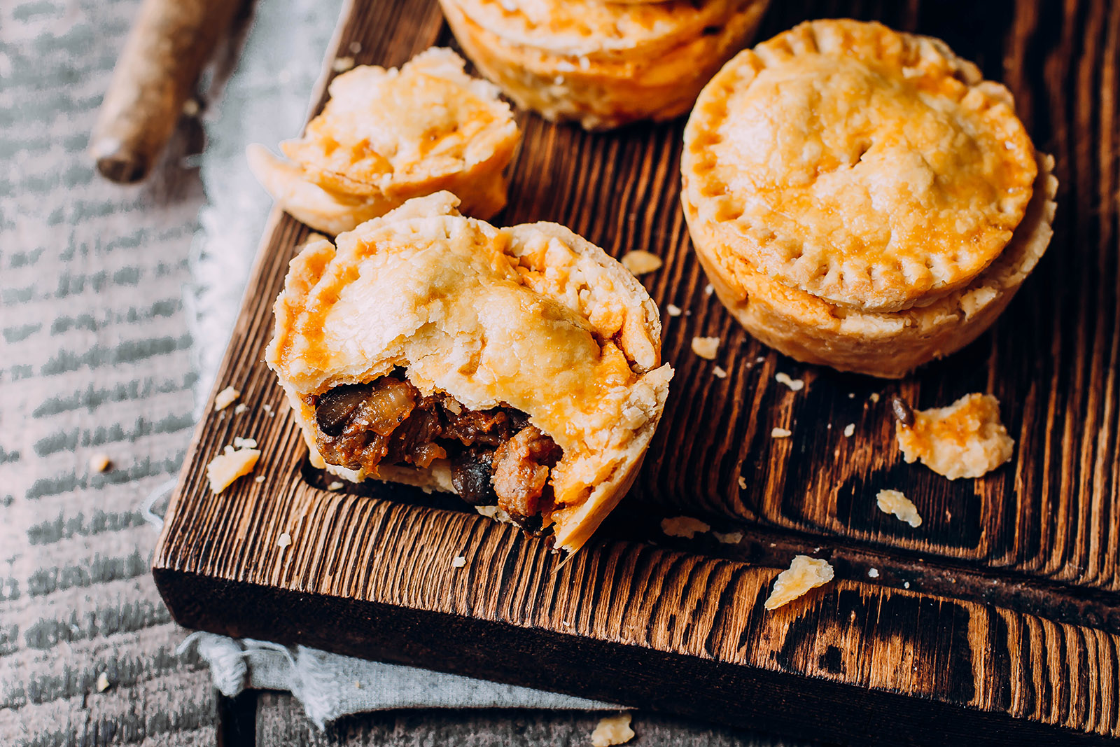 flaky meat pies displayed on a wooden cutting board