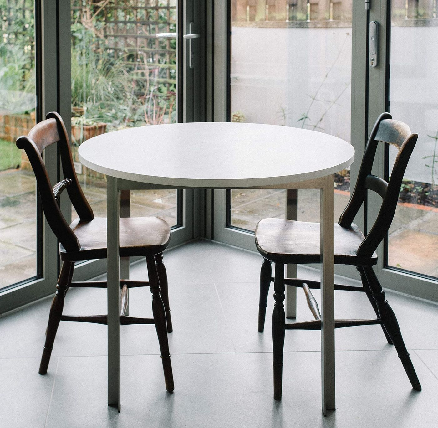 Detail view of the bespoke breakfast table designed and manufactured by From Works of stained light grey birch plywood timber top and stainless steel angle legs.