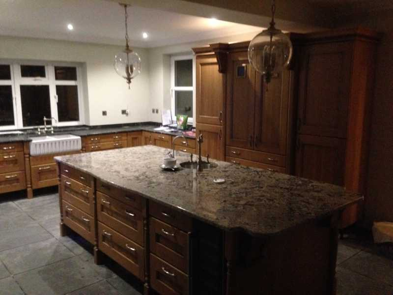Oak kitchen with granite worktops and sink within a central island