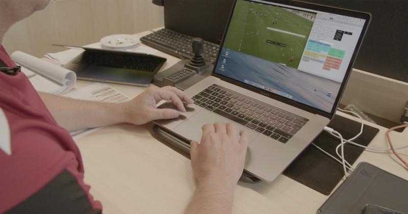 ノート PC でサッカー映像を分析する男性