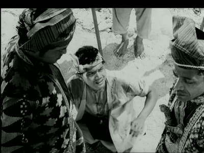 A black and white film still from the movie, 'Hang Jebat'. Three men are in the scene.