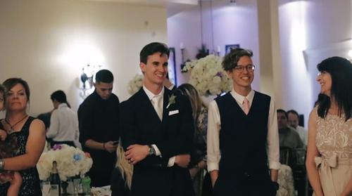 Groom smiling at Bride at reception