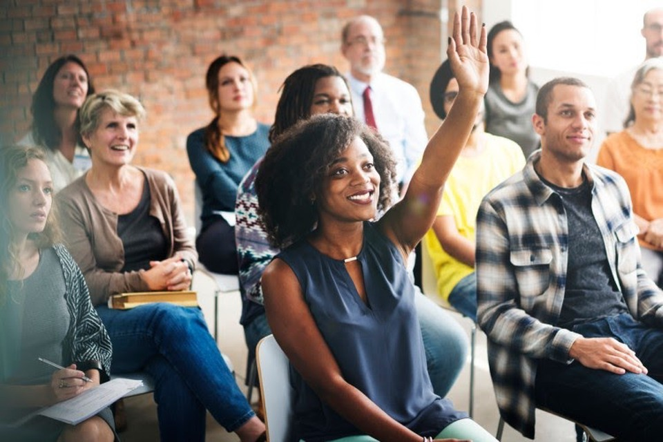 A smiling person raises their hand during an education program in a workplace.