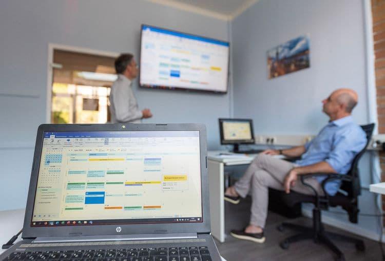 Trainer erklärt im Hamburger Schulungsraum mit 3 Teilnehmern Outlook an Fernseher