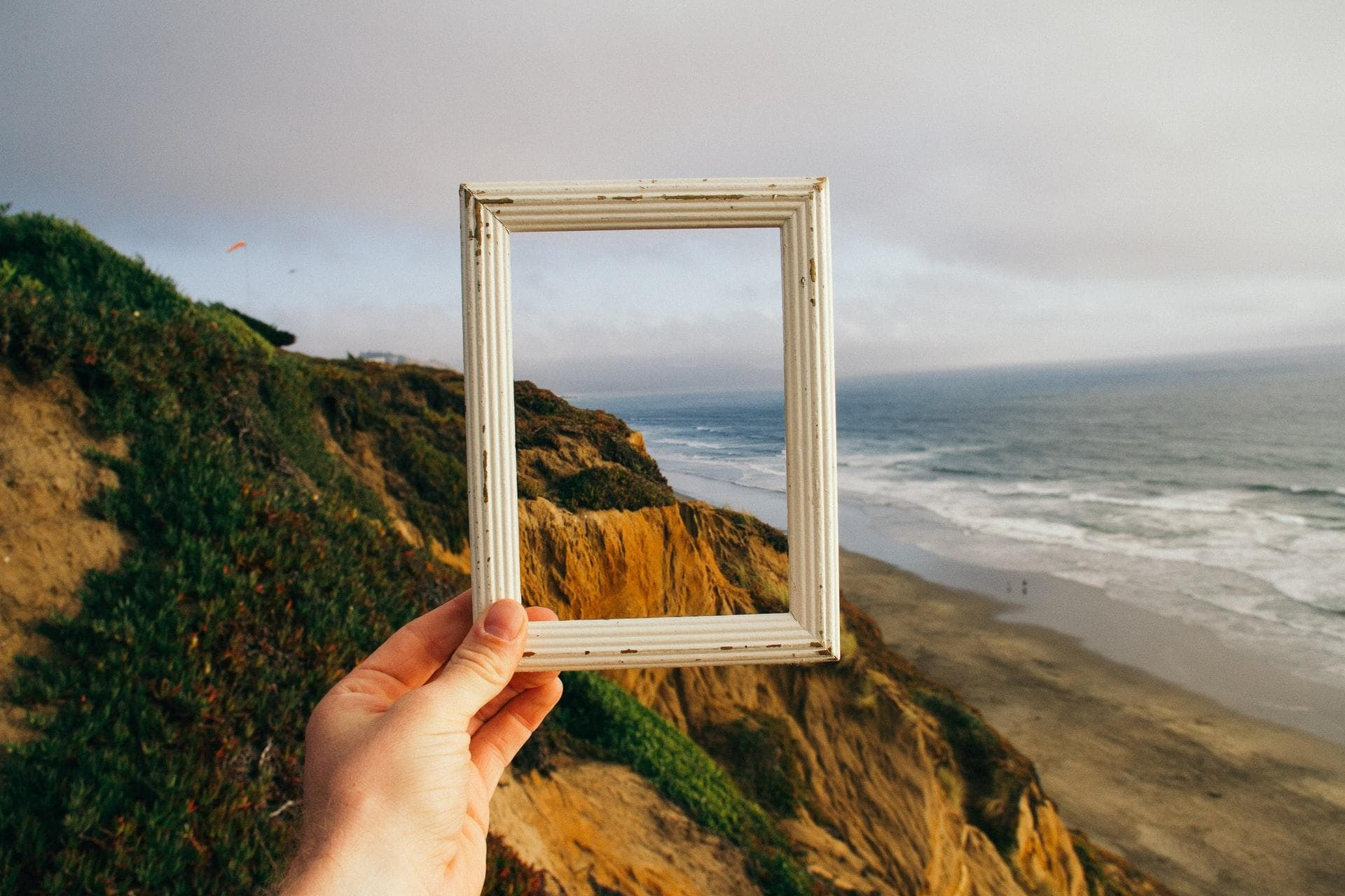 A white picture frame in front of a landscape with a beach.