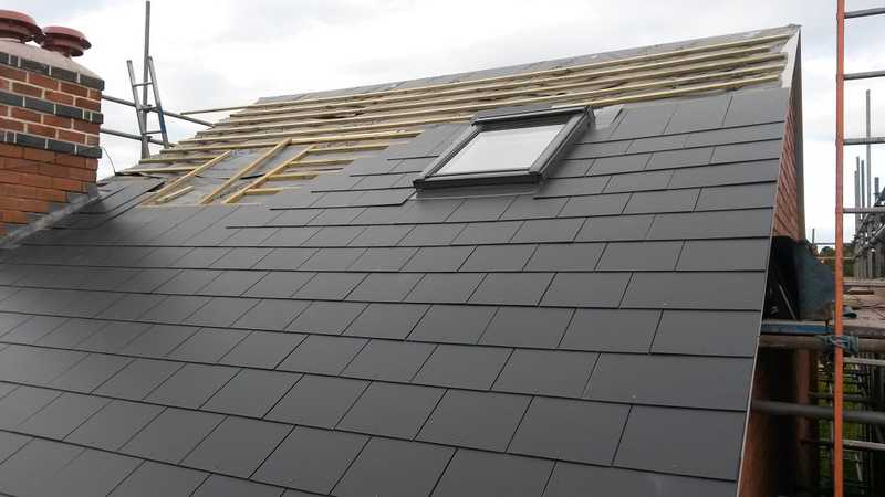 A roof being repaired for a client property, having a new Velux skylight installed along with slate tiling