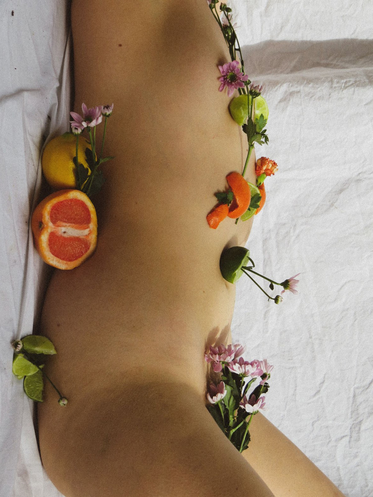 Image of a body covered in citrus fruits and flowers