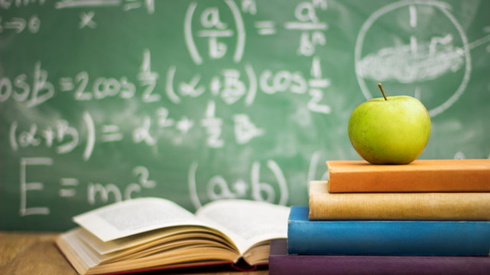 Four books on a table with a green apple above it. There's a black board behind with Physics equations.
