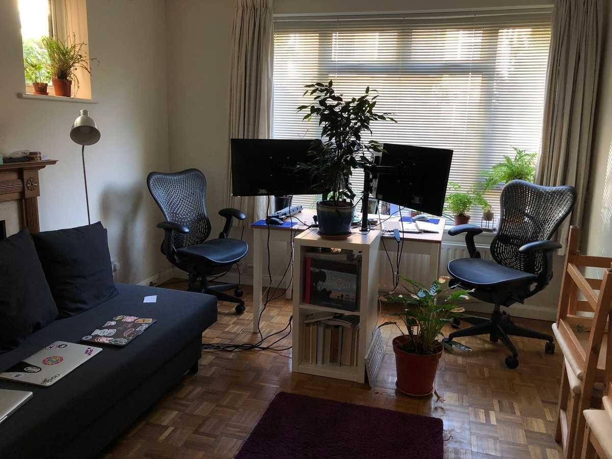 Our living room, a sofa, rug, long desk, two setups