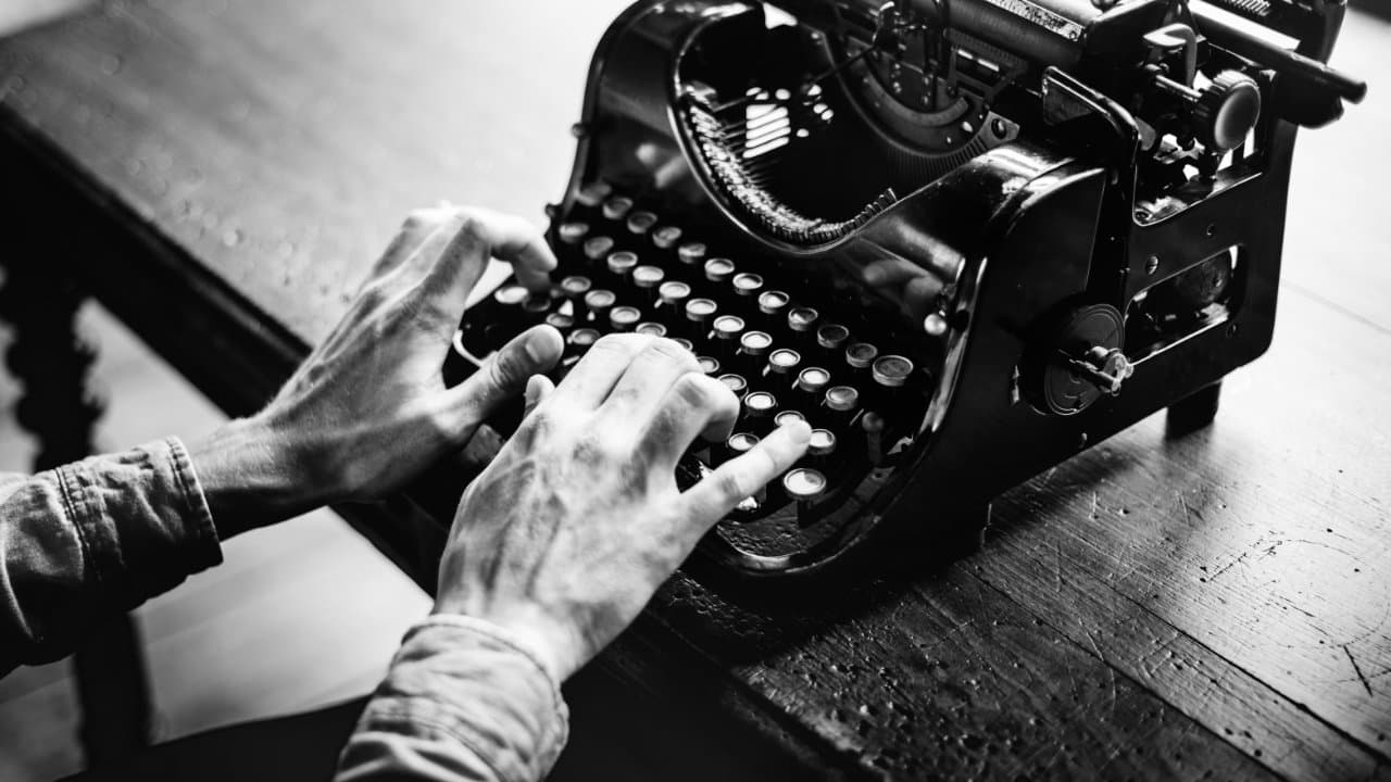Monochrome image of typing on an old typewriter