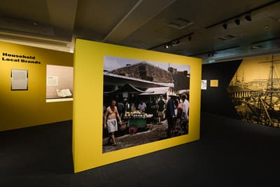 An island wall in the middle is predominantly showing a photo of a street market. In the background to the left, a wall is titled 'Household Local Brands'. On the right, a wall features a black and white illustration of a ship at a dock.