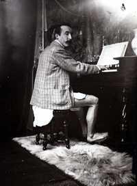 Gauguin, c. 1895, playing a harmonium at Alphonse Mucha's studio at rue de la Grande-Chaumière, Paris