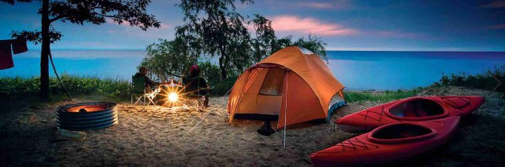 camping with tent and campfire and kayaks