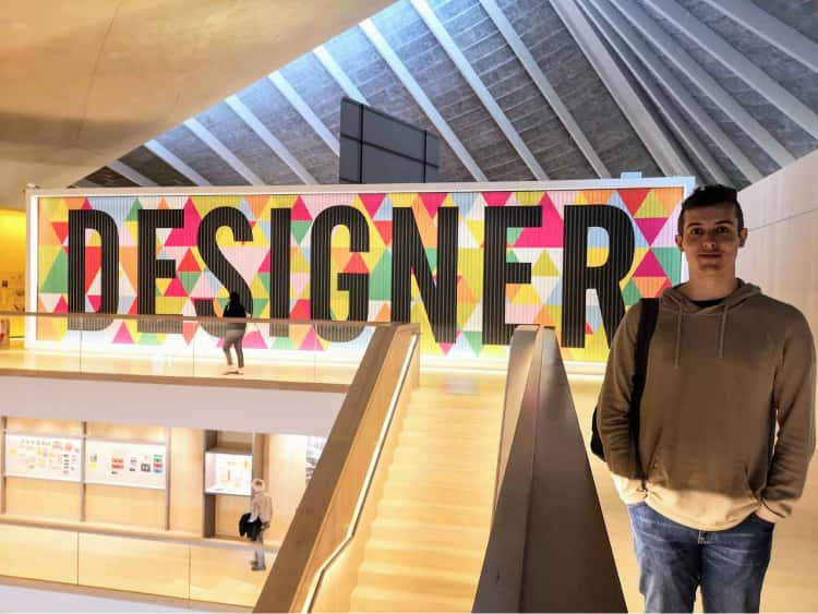 Myself stood on the top floor of the Design Museum in London, with a large display in the background (the height of the walls) displaying the word DESIGNER, with a geometric pattern surrounding it.