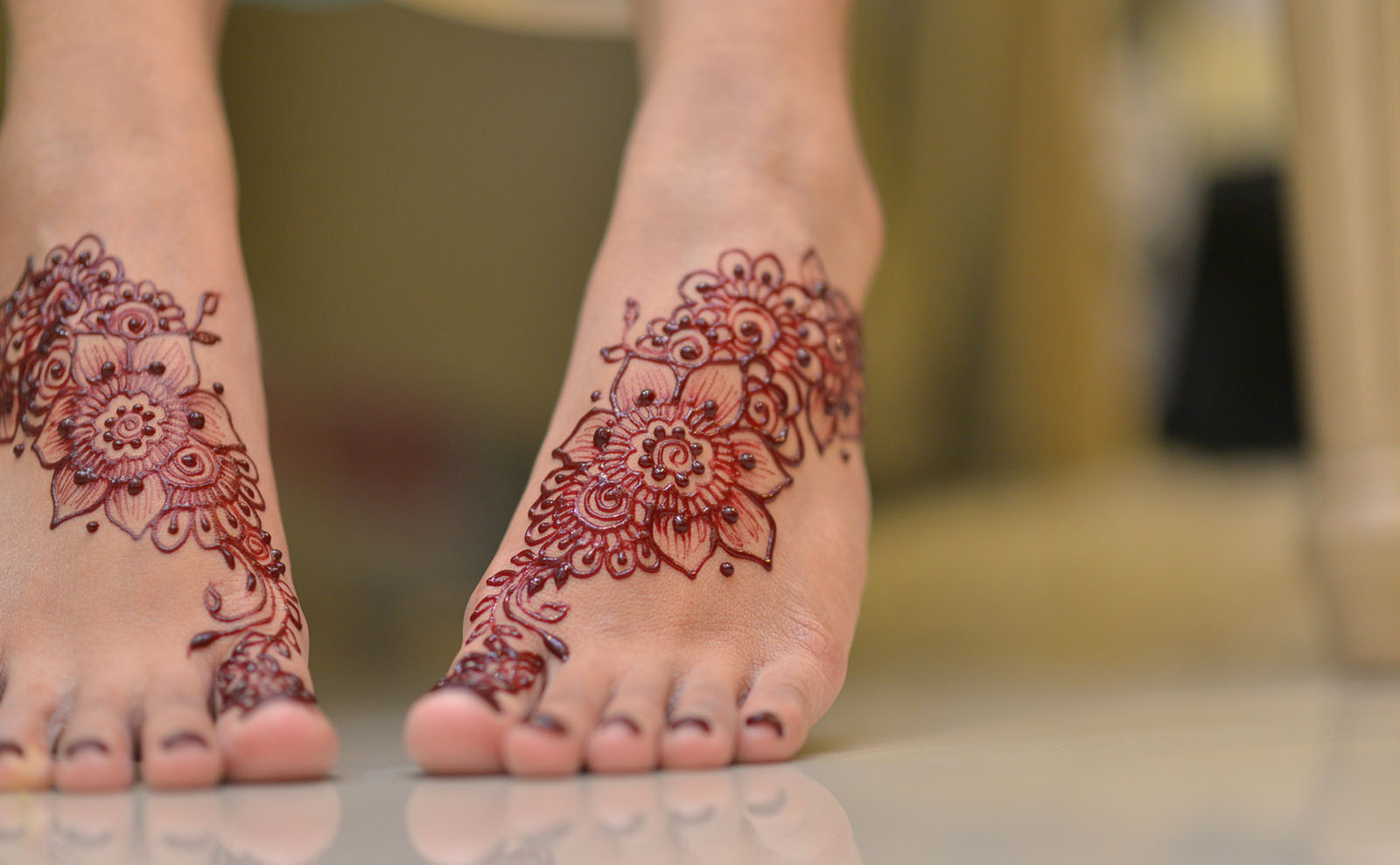 a woman's feet displaying black henna tattoos