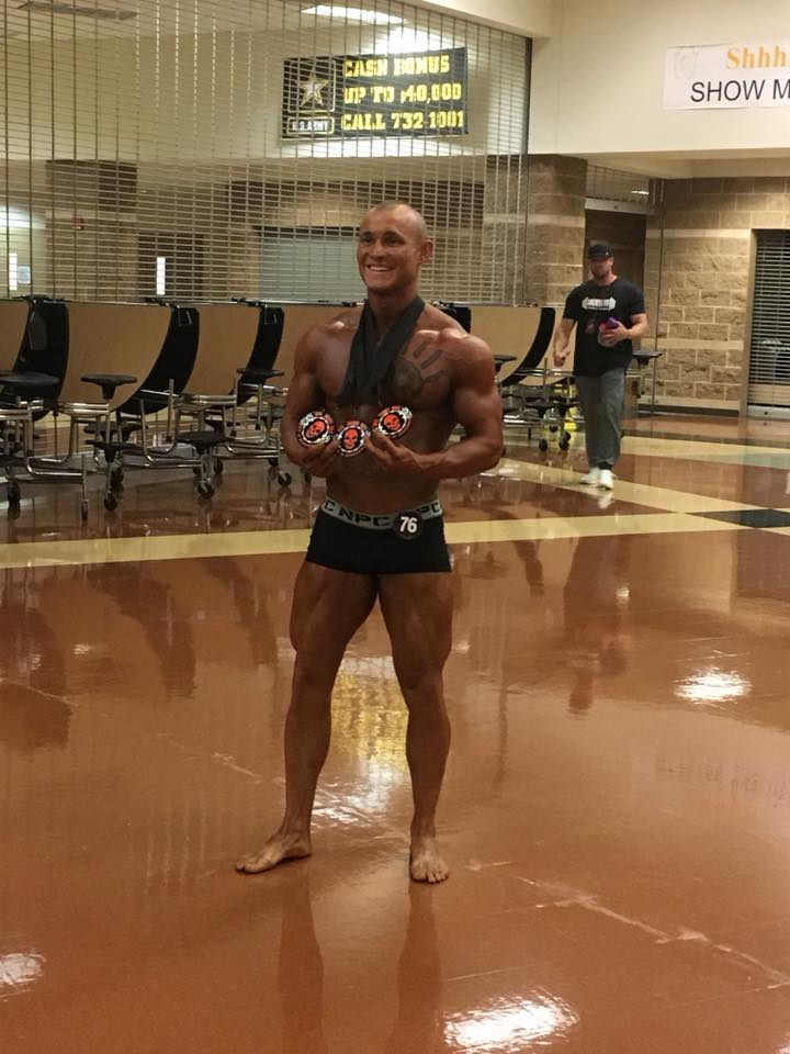 A heavily muscled, almost nude man stands smiling broadly in an empty gymnasium, proudly displaying three competitive medals hanging on ribbons around his neck. His tanned and sculpted body features a large chest tattoo of a hand.