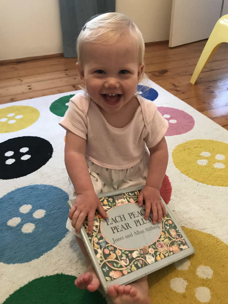 Competition winner Sienna with her favourite book, <cite>Each Peach Pear Plum</cite>