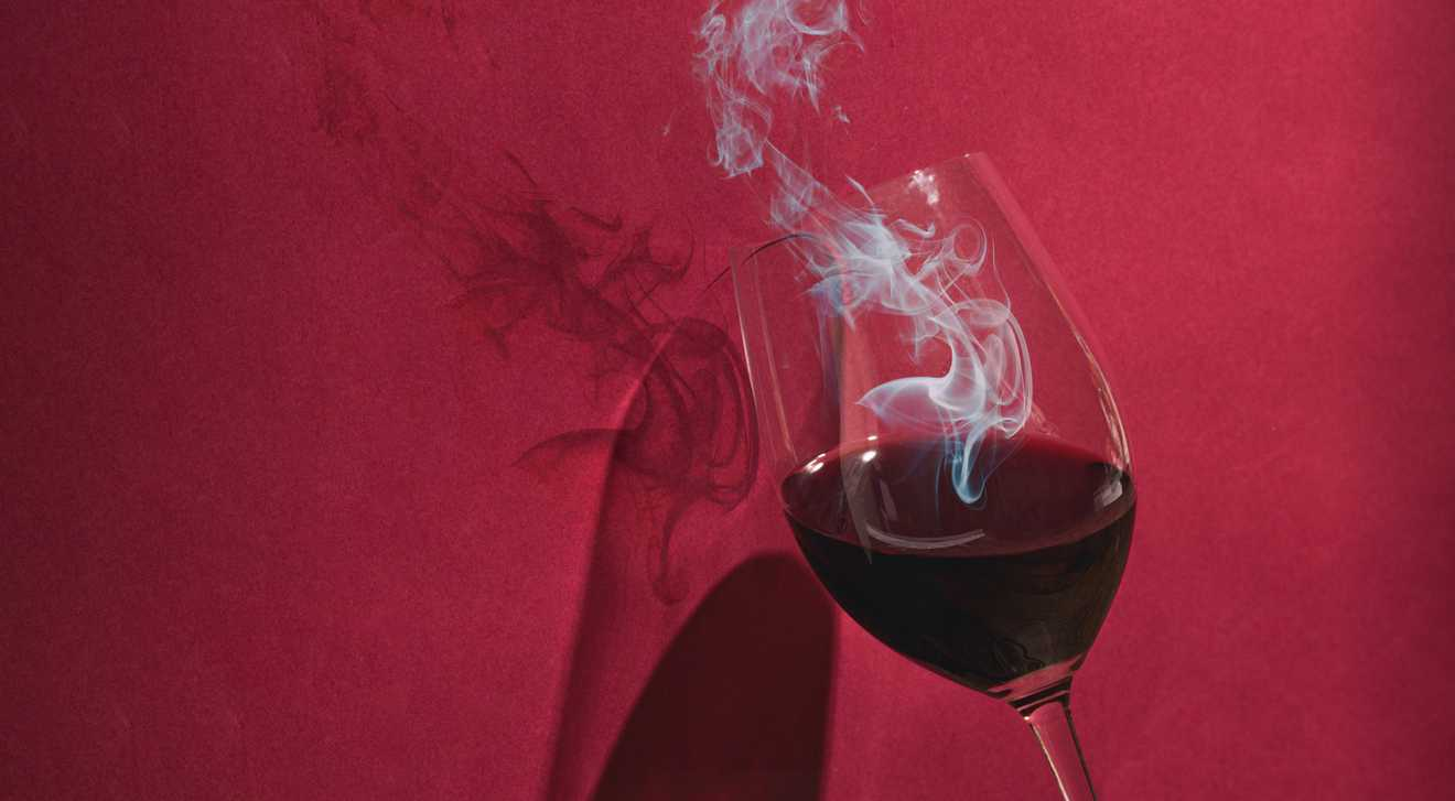Photo illustration of fire coming out of a wine glass to illustrate smoky tasting wine