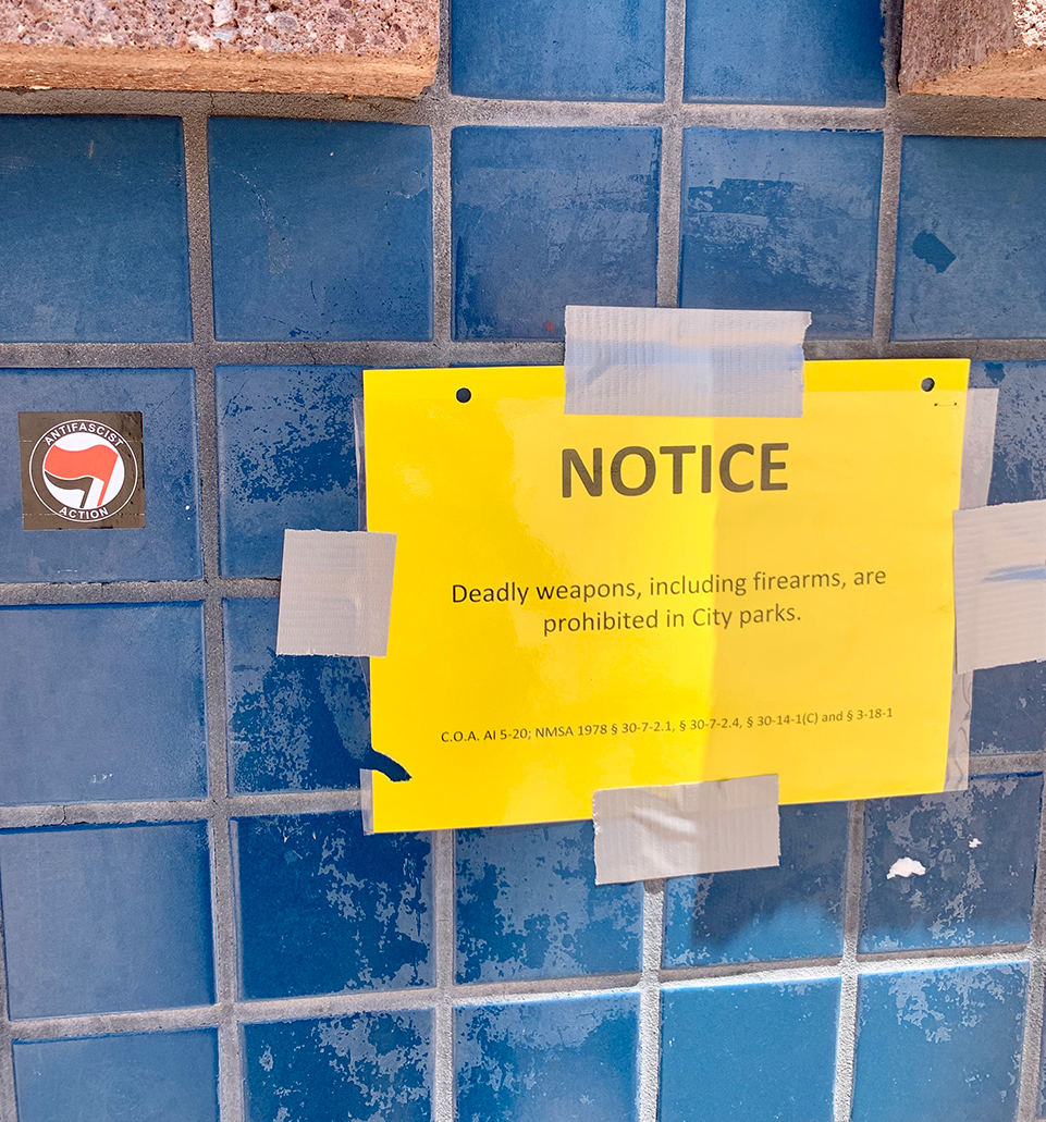 A copy of the city's firearms ban posted in the plaza on July 19, alongside an antifascist action sticker. Photo by Bella Davis.