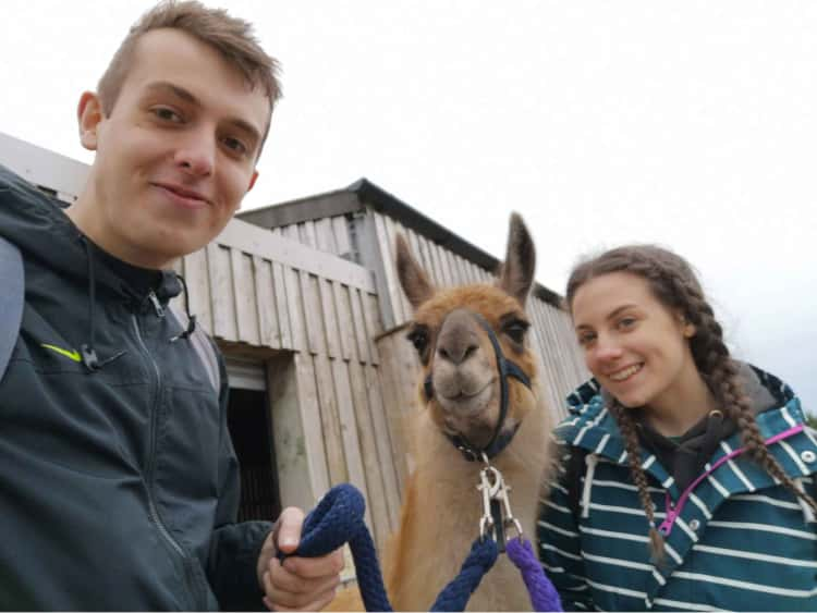 Myself and Naomi stood either side of a Llama (called Sid), that we walked. Somehow we're all smiling, stood in front of a wooden shed.