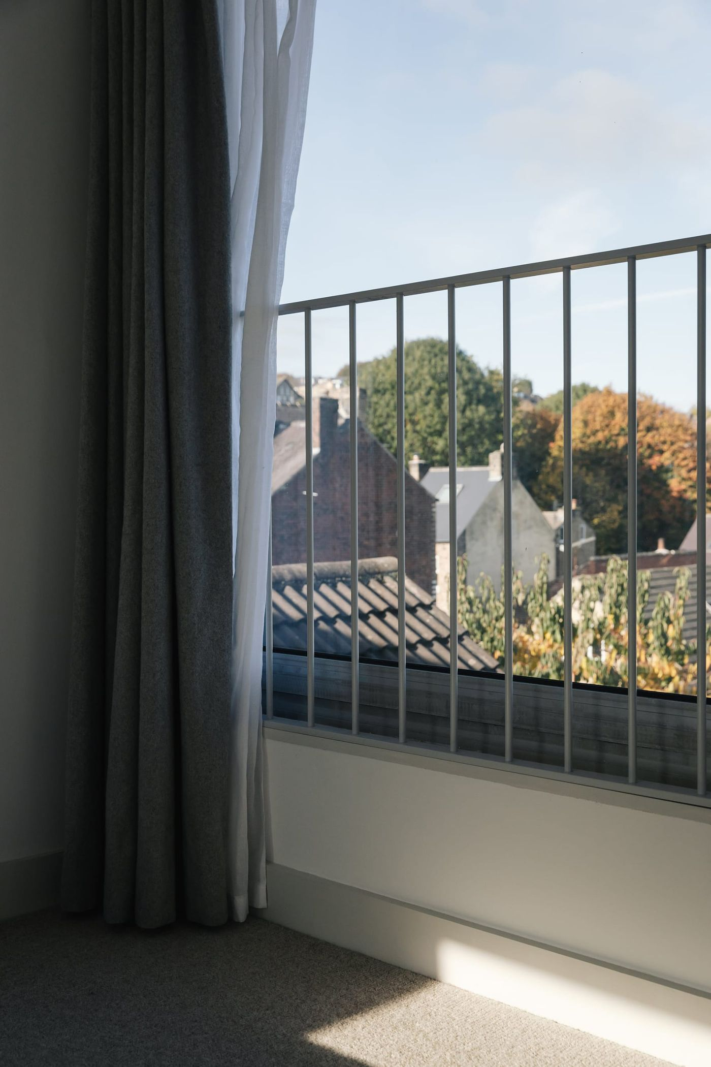 Interior view looking towards the countryside with with open juliet balcony, voile and grey felt curtains in the white and grey light filled bedroom within From Works loft conversion and rear dormer extension in Walkley, Sheffield.