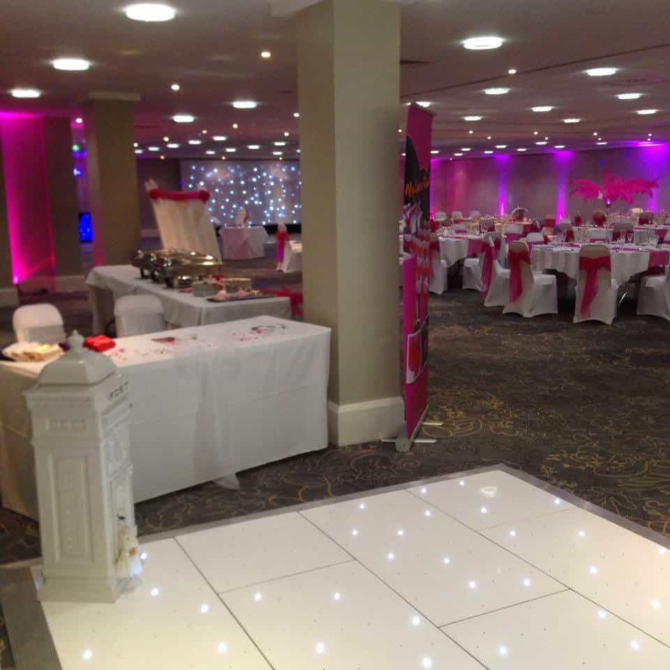 Wedding venue dressing with pink lighting, chair decor. White table linens, white dancefloor and white postbox.