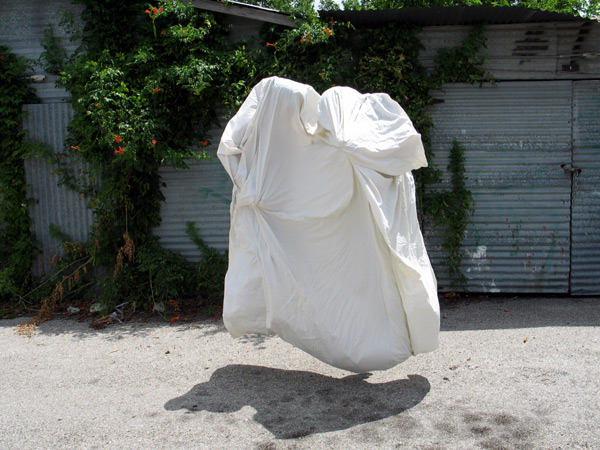 A plain cotton sheet floats above the ground, seems to be inhabited by two human bodies.