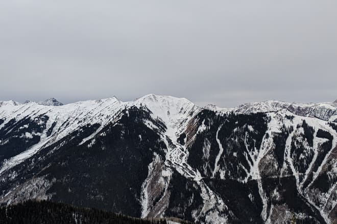 A bowl-shaped area of a snow-covered chain of mountains. The winter sky above is cold and gray.