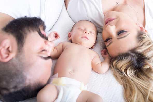 liggende baby met ouders om zich heen