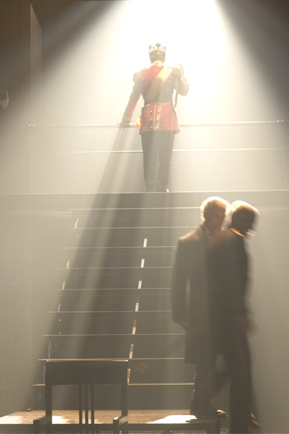 King stands facing away at top of stairs in shaft of strong back light.