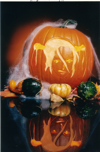 A pumpkin with a carving of an anime character sits on top of a glass surface.