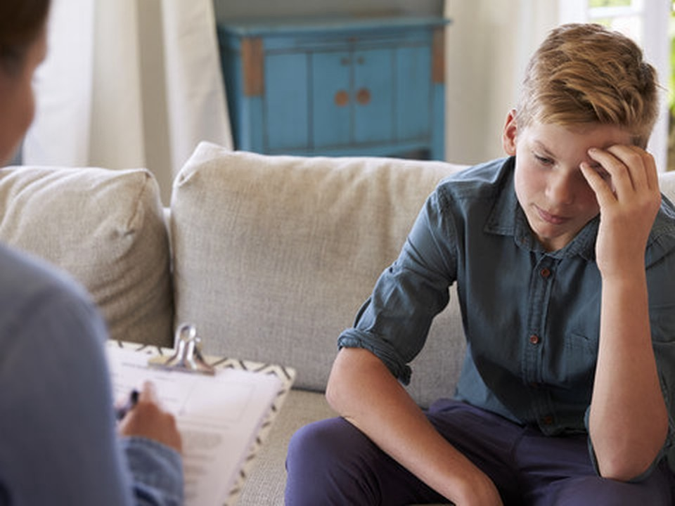 A teenager boy seated at a sofa looking at the floor while a woman talks to him