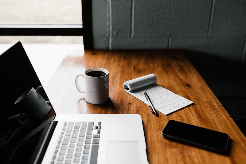 Uma mesa com alguns utensílios em cima: um notebook, uma xícara de café, um celular e um bloco de notas com uma caneta em cima