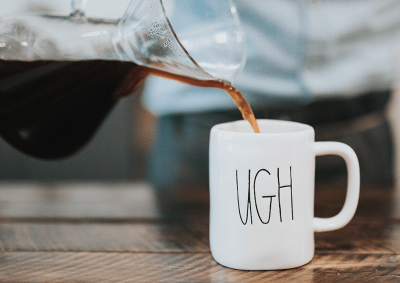 "person pouring coffee on mug with ""ugh"" printed"