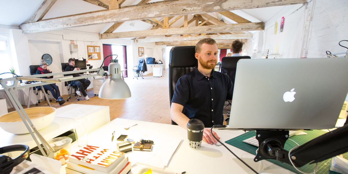 A digital designer sitting in an office at a MacBook Pro