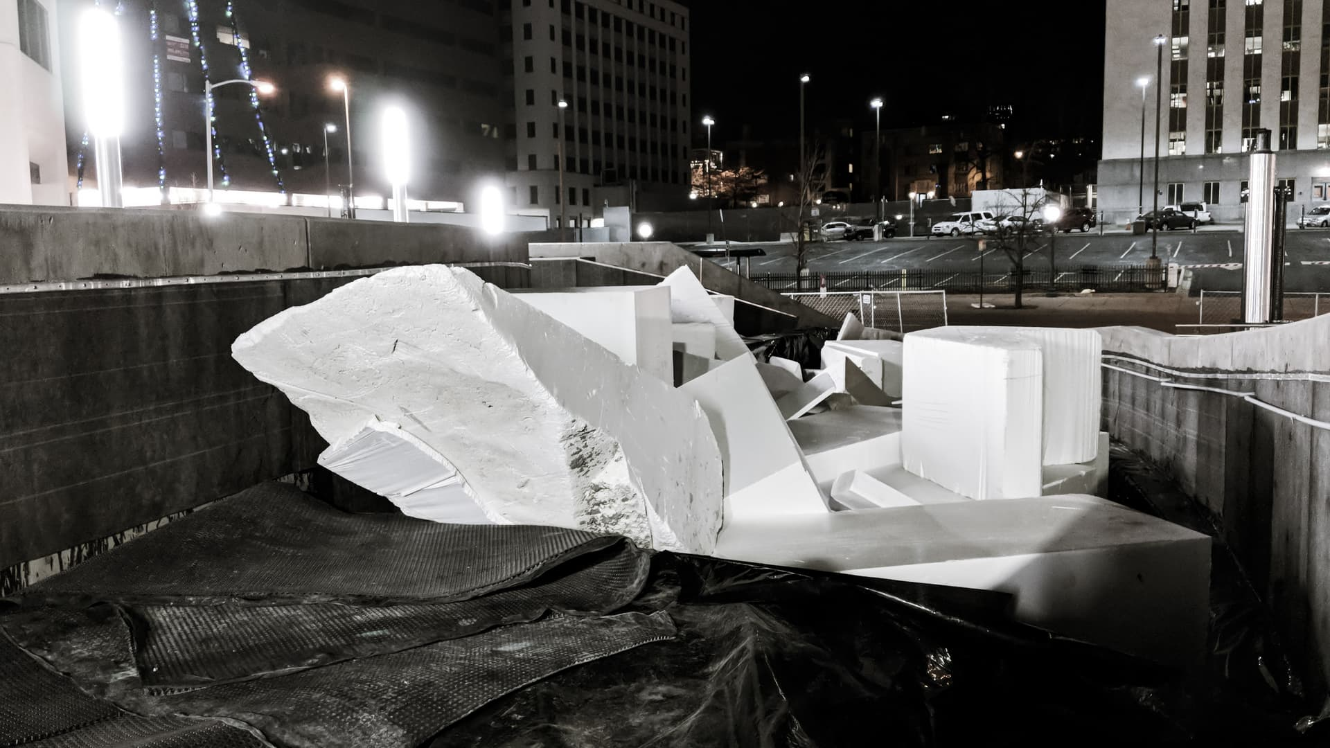 A picture of a debris pile near a construction site at night. Car-sized pieces of styrofoam, almost crystalline in appearance, dominate the center of the frame.
